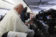 Pope Francis greets journalist on board of a plane on his way to Dublin, Ireland, Saturday, Aug. 25, 2018. Pope Francis is on a two-day visit to Ireland. (AP Photo/Gregorio Borgia, Pool)
