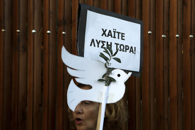 "A protestor holds a placard reading in Greek ""Go solution now"" during a peace protest from Greek and Turkish Cypriots outside the presidential palace in the divided capital Nicosia, Cyprus, Thursday, Oct. 25, 2018. President Nicos Anastasiades, who leads the country's internationally recognized government, and the leader of the breakaway Turkish Cypriots, Mustafa Akinci, are being hosted for a meeting by Elizabeth Spehar, the head of the U.N.'s peacekeeping force in Cyprus, on Oct. 26, 2018. (AP Photo/Petros Karadjias)"