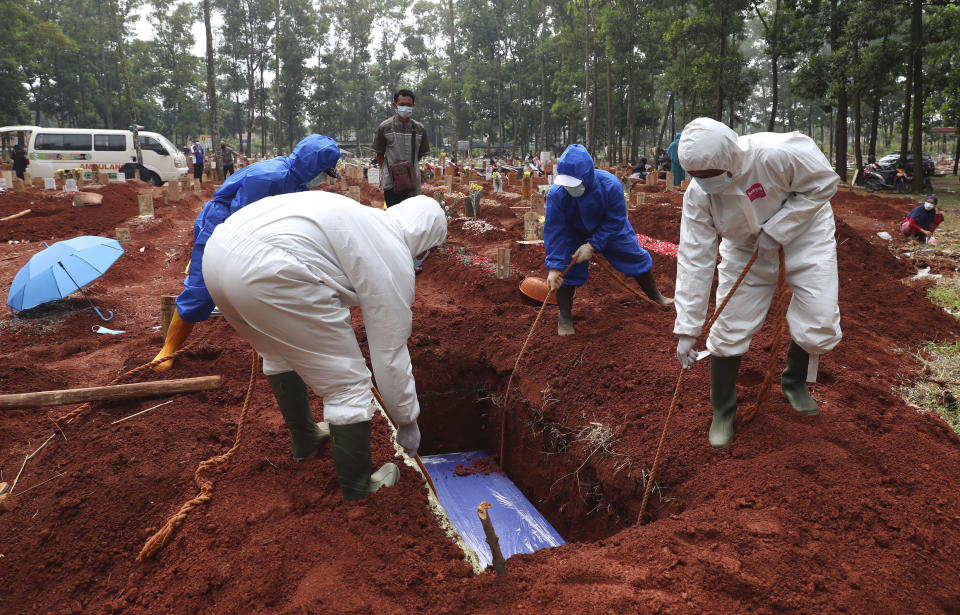 In this July 14, 2021, photo, workers in protective gear lower a coffin of a COVID-19 victim to a grave for burial at the Cipenjo Cemetery in Bogor, West Java, Indonesia. Images of bodies burning in open-air pyres during the peak of the pandemic in India horrified the world in May, but in the last two weeks Indonesia and two other Southeast Asian nations have surpassed India's peak per capita death rate as a new coronavirus wave tightens its grip on the region. (AP Photo/Achmad Ibrahim)