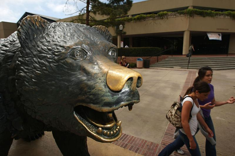 Students pass the bronze statue of their campus mascot, The Bruin, a California grizzly bear, at University of California, Los Angeles (UCLA). (Photo by David McNew/Getty Images)