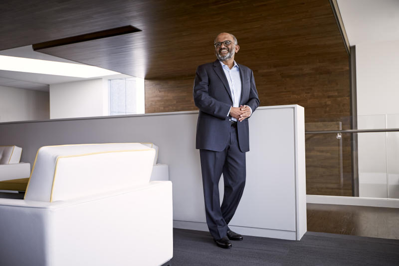Adobe CEO Shantanu Narayen standing in the company's contemporary office space.