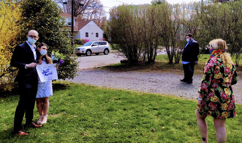 In this April 11, 2020, photo provided by Michael Wargo, newlyweds Danielle Cartaxo and Ryan Cignarella pose after getting married in West Orange, N.J. Barred from getting married in a public space due to lockdown restrictions, Cartaxo and Cignarella got married on the front lawn of the home of a stranger who offered to help. (Michael Wargo via AP)