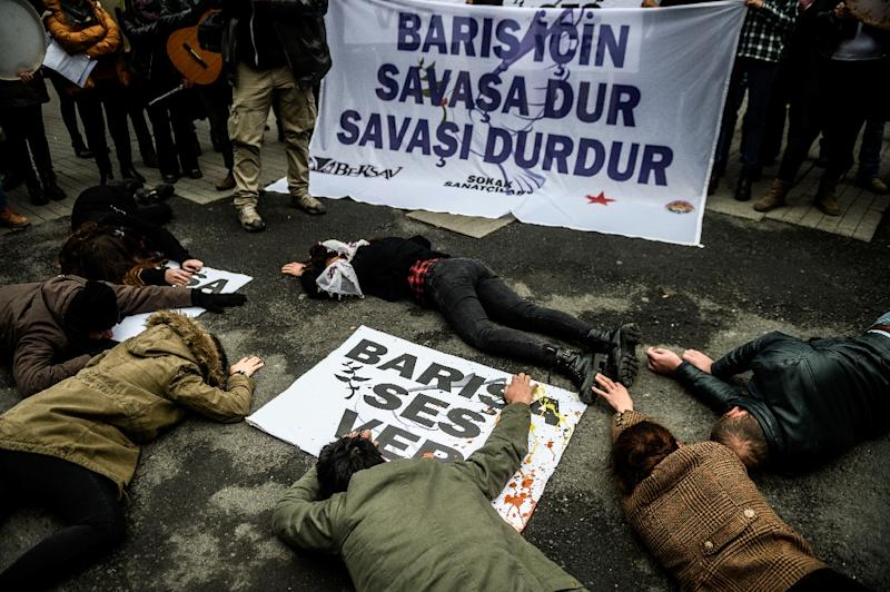 "A group of street artists lie on a sign reading ""To get Peace, stop the War! Make noise for Peace!"" during a demonstration on January 10, 2016 in Istanbul, after Turkish security forces killed 18 militants from the Kurdistan Workers' Party (PKK)"