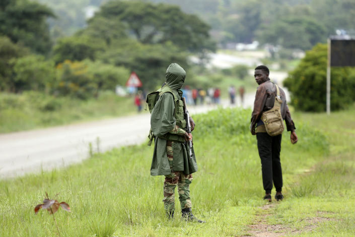 A soldier patrols as protestors gather during a demonstration over the hike in fuel prices in Harare, Zimbabwe, Tuesday, Jan. 15, 2019. A Zimbabwean military helicopter on Tuesday fired tear gas at demonstrators blocking a road and burning tires in the capital on a second day of deadly protests after the government more than doubled the price of fuel in the economically shattered country. (AP Photo/Tsvangirayi Mukwazhi)