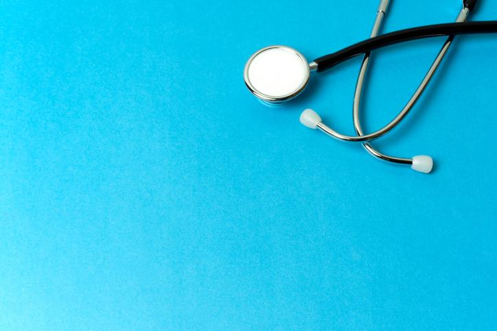 A stethoscope sitting on a blue background.