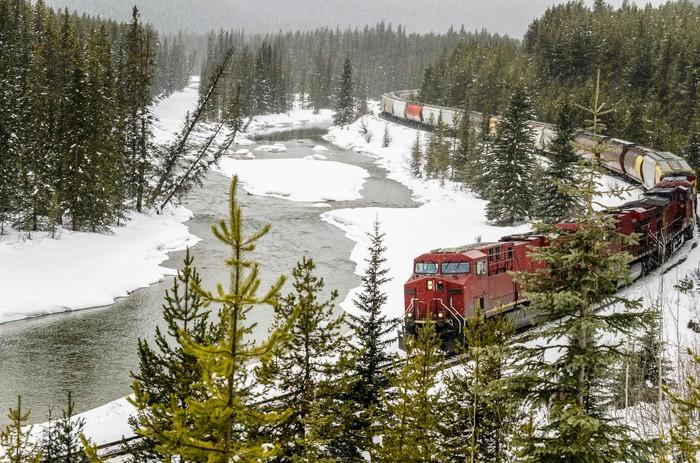 A freight train next to a stream and snowy forest
