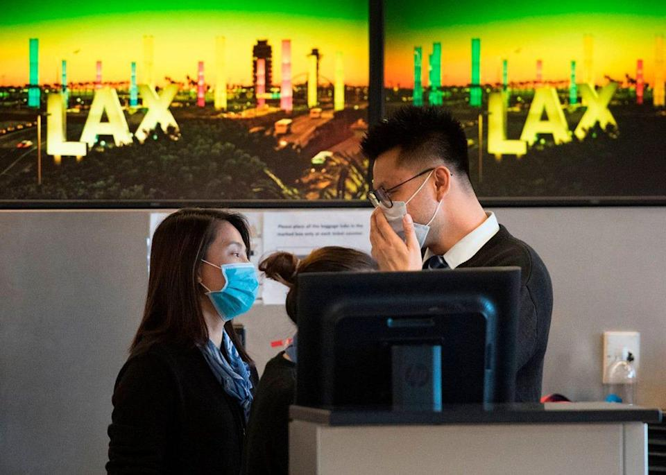 Airline staff wear face masks to protect against the spread of coronavirus at the Los Angeles International Airport on Jan. 29.