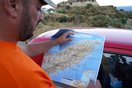 A volunteer rescuer watches a map of the area where the body of missing 35-year-old British Natalie Christopher was found on the island of Ikaria
