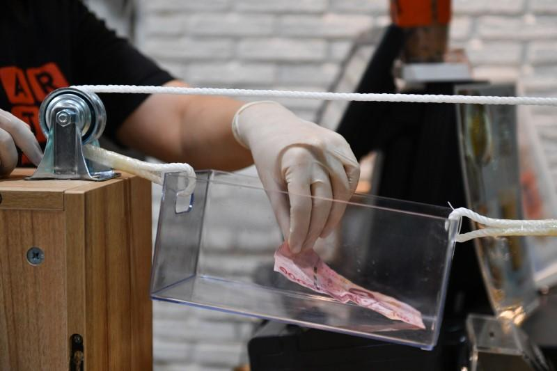 A barista puts money back in a box pulled by a rope as a transportation system after a cafe adopted a social distance policy for their customers amid fears of coronavirus outbreak in Bangkok