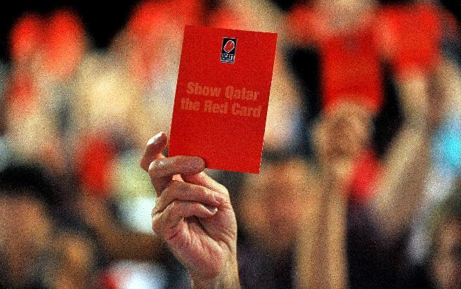 Delegates hold cards with the words, 'Show Qatar the Red Card' as they demonstrate support for better conditions for workers building stadiums and infrastructure for the 2022 World Cup in Qatar, in Liverpool on September 10, 2014 (AFP Photo/Paul Ellis)