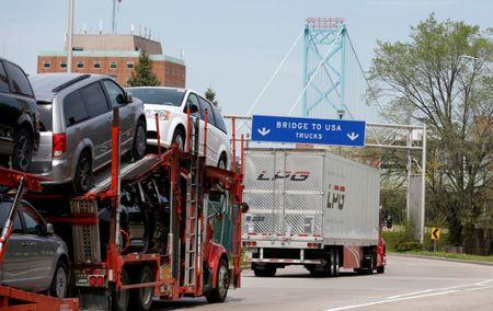 Semi trucks heading for Detroit, Michigan, drive on the lane to Ambassador Bridge in Windsor
