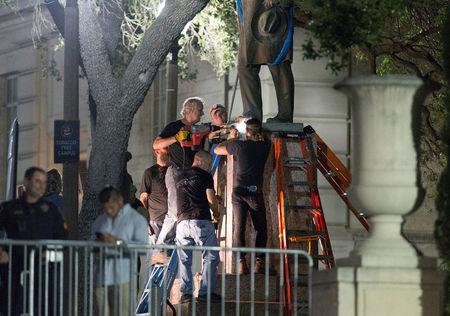 Workers remove Confederate Postmaster General John Reagan statue from the south mall of the University of Texas in Austin, Texas, U.S., August 21, 2017. REUTERS/Stephen Spillman