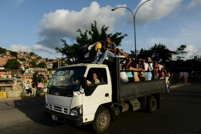 People ride on a truck turned bus in a Caracas slum -- one way to deal with a transport mess that is part of Venezuela's economic crisis