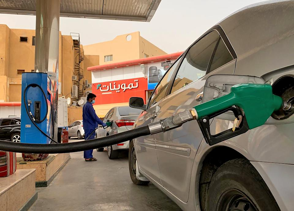 A gas station attendant refills a car at a station in the Saudi capital Riyadh on May 11, 2020. - Saudi Arabia's energy ministry said it had asked oil giant Aramco to make an additional voluntary output cut of one million barrels per day starting from June to support prices. The move will reduce the production of the world's biggest crude exporter to 7.5 million barrels per day, the energy ministry said in a statement cited by the official Saudi Press Agency. (Photo by RANIA SANJAR / AFP) (Photo by RANIA SANJAR/AFP via Getty Images)