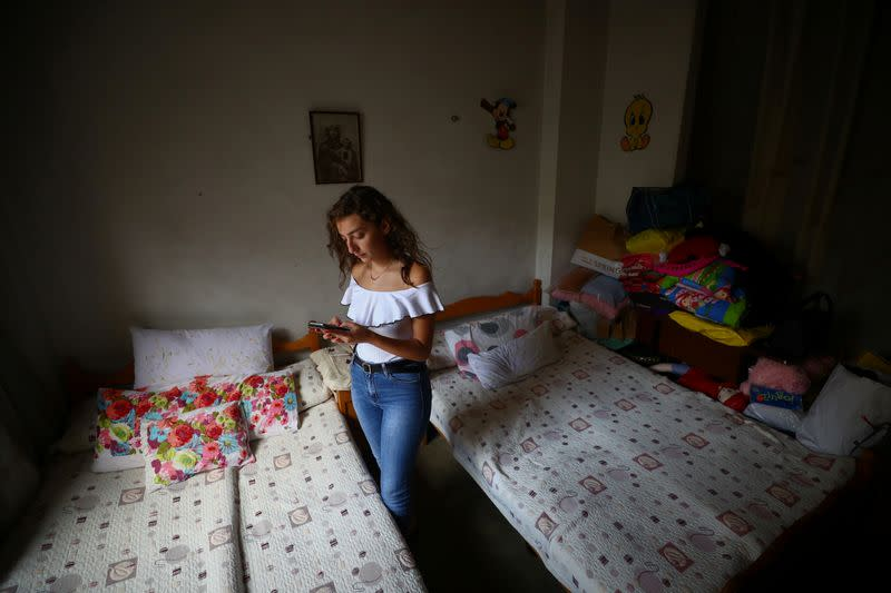 Tatiana Hasrouty uses her mobile phone next to the bed of her father Ghassan Hasrouty, a missing silo employee, following Tuesday's blast in Beirut's port area