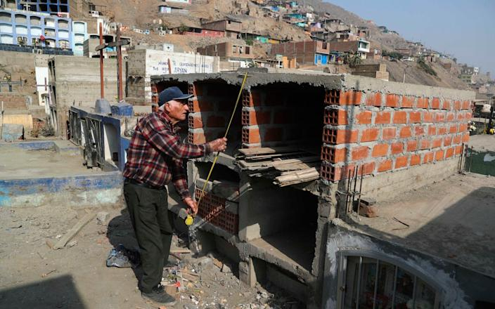 Victor Coba takes measurements of the tombs he's building for his family at San Lazaro cemetery on the outskirts of Lima, Peru - Martin Mejia/AP