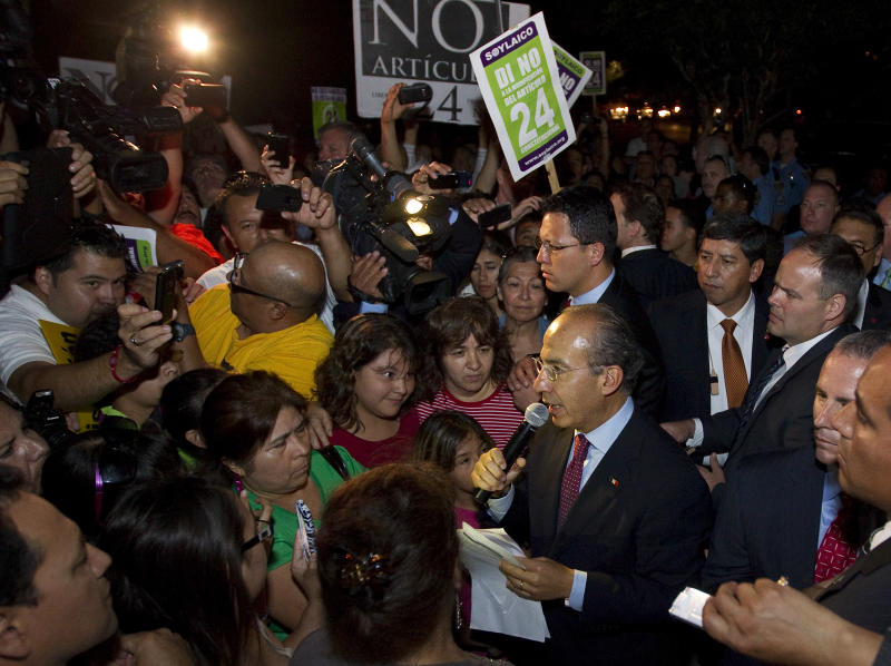 Mexican President Felipe Calderon, center, address a crowd that gathered to protest the possible changes to in article 24 of the Mexican constitution, Wednesday, April 25, 2012, outside the Ripley House community center in Houston. The draft legislation proposes changes in the language of Articles 24 and 40 of the Mexican Constitution, guaranteeing religious instruction in Mexican schools, and allowing the church greater access to mass means of communication, among other things. (AP Photo/Houston Chronicle, Nick de la Torre)