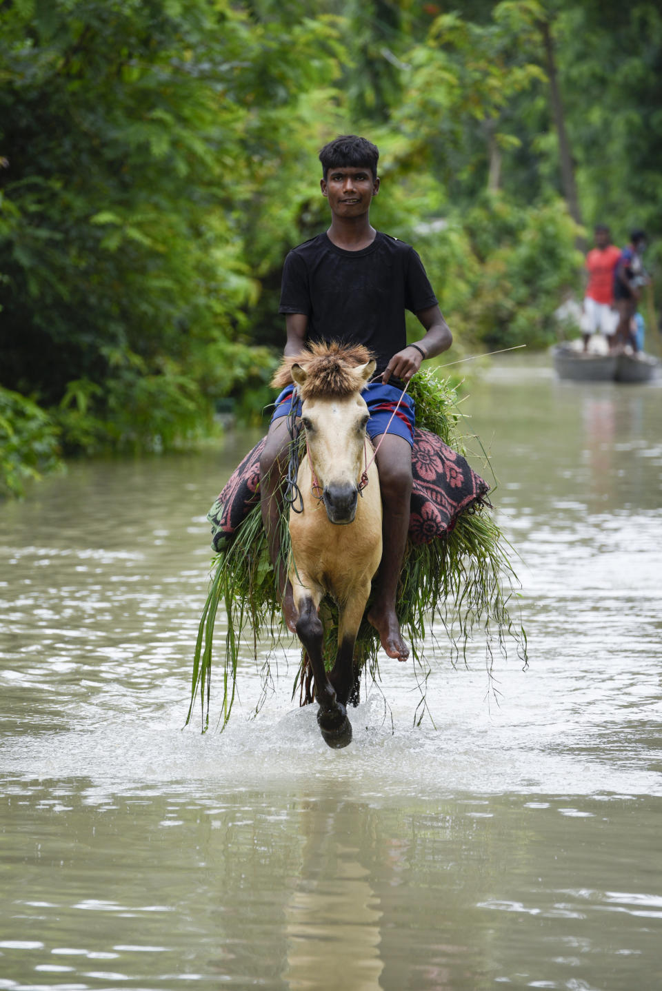 A boy rides a donkey as he id croosing a flooded street in a village in Kamrup district of Assam, in India on 14 July 2020. (Photo by David Talukdar/NurPhoto via Getty Images)