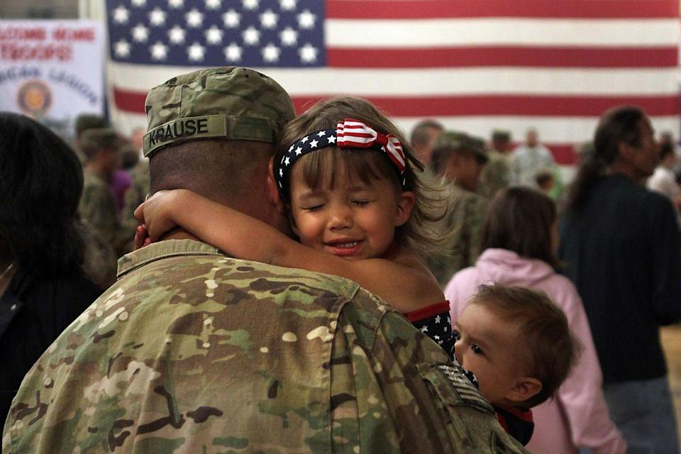 <p>Reniah Krause, 2, clings to her father Sgt. Joseph Krause after he and fellow soldiers return home from Afghanistan. More than 500 soldiers from the 1st Brigade Combat Team came back that day following a year of heavy fighting and numerous casualties in Afghanistan's southern Kandahar province. </p>