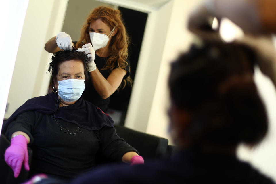 A young hairdresser and a customer wearing face masks and gloves to protect against the coronavirus in a salon in Bressanone, known in German as Brixen, Italy, Monday, May 11, 2020. The northern Italian province of South Tyrol is moving ahead of policies by the central government, reopening restaurants and shops closed during the coronavirus crisis earlier than planned by Rome. (AP Photo/Matthias Schrader)
