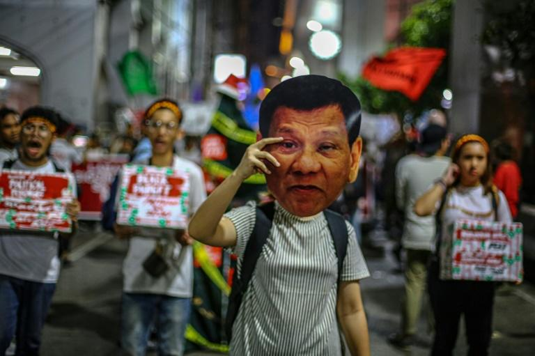 A human rights advocate holds up a mask featuring Philippine President Rodrigo Duterte during a rally in Manila