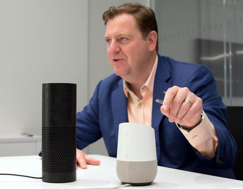 In this June 14, 2018, photo, Gareth Gaston, Executive Vice President and Head of Omnichannel Banking at US Bank, discusses voice assistant banking with an Amazon Echo, left, and a Google Home, right, in New York. Big banks and financial companies have started to offer banking through virtual assistants, Amazon's Alexa, Apple's Siri, and Google's Assistant, in a way that will allow customers to check their balances, pay bills and, in the near future, send money just with their voice. Regional banking giant U.S. Bank is the first bank to be on all three services, Alexa, Siri and Assistant. (AP Photo/Mark Lennihan)