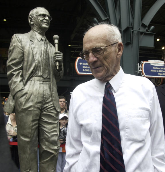 FILE - In this Sept. 15, 2002 file photo, Detroit Tigers Hall of Fame broadcaster Ernie Harwell pauses near a statue honoring him that was unveiled inside the entrance to Comerica Park in Detroit. Their voices are the backdrop to all those warm summer nights. Their distinctive calls are part of the games lore. Fans visualize the action through their stories and descriptions. (AP Photo/Paul Sancya, File)