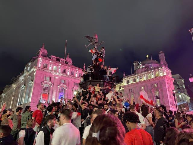 England football fans climb the statue of Eros in Piccadilly Circus, central London