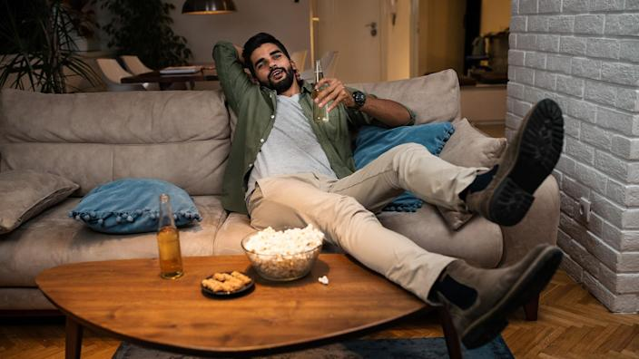 Young man lying on couch watching TV.
