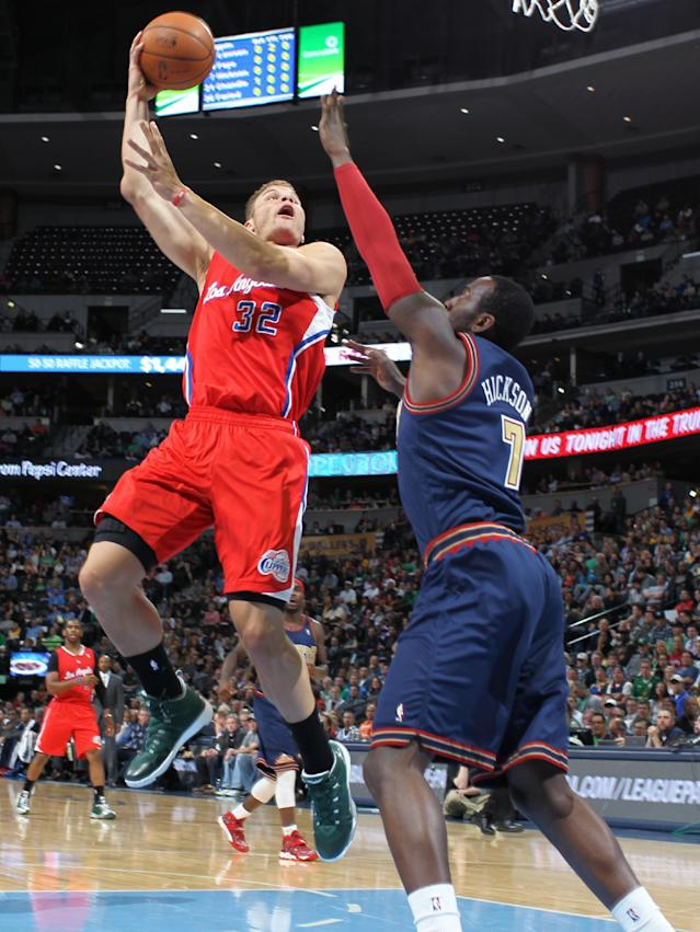 Los Angeles Clippers forward Blake Griffin, left, flies through lane to make a hook shot for a basket over Denver Nuggets forward J.J. Hickson in the first quarter of an NBA basketball game in Denver on Monday, March 17, 2014. (AP Photo/David Zalubowski)