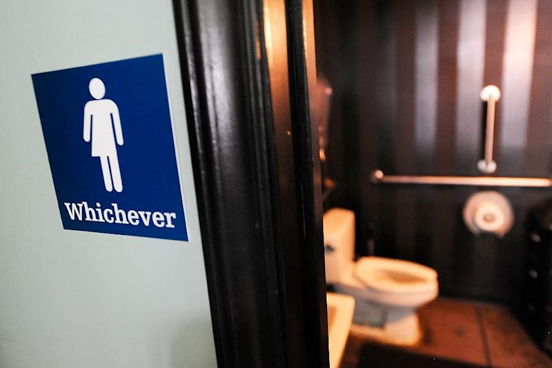 A gender neutral sign is posted outside a bathrooms at Oval Park Grill on May 11, 2016 in Durham, North Carolina