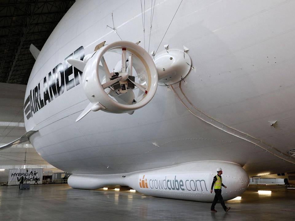 the exterior of the Airlander 10 in a hangar with someone walking by