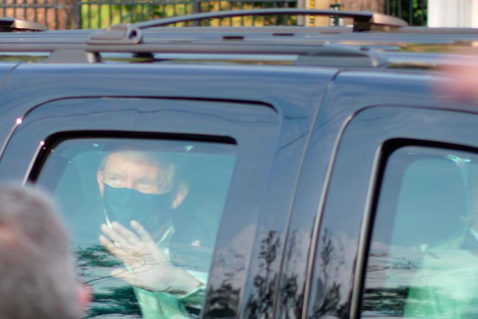 President Donald Trump waves to supporters gathered outside Walter Reed National Military Medical Center in Bethesda, Maryland, on Sunday. At least two other people were in the vehicle with him. (Photo: ASSOCIATED PRESS)