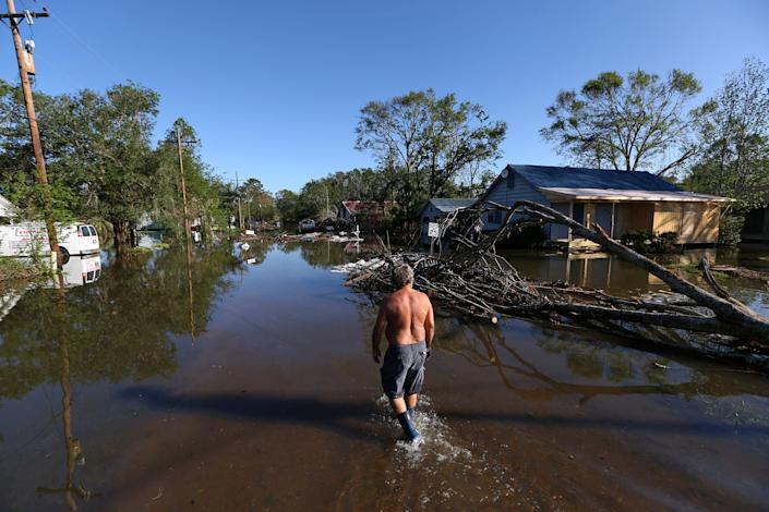 Image: Brian Schexnayder walks down a flooded street after Hurricane Delta in Iowa (Jonathan Bachman / Reuters)
