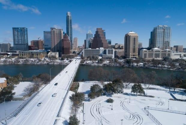 A snow-covered Ann Richards Congress Avenue Bridge leads to downtown after a heavy snowfall on Monday, Feb. 15, 2021, in Austin, Texas.