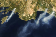 In this Tuesday, Aug. 3, 2021, Aqua satellite Moderate Resolution Imaging Spectroradiometer (MODIS) image taken in natural color and provided by NASA, several wildfires burn near the coastal towns of Marmaris, left, and Antalya, along the southern coast of Turkey. (NASA via AP)