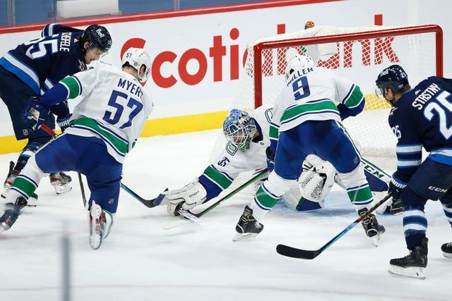 Vancouver Canucks goaltender Thatcher Demko covers the puck from Winnipeg Jets' Mark Scheifele and Paul Stastny