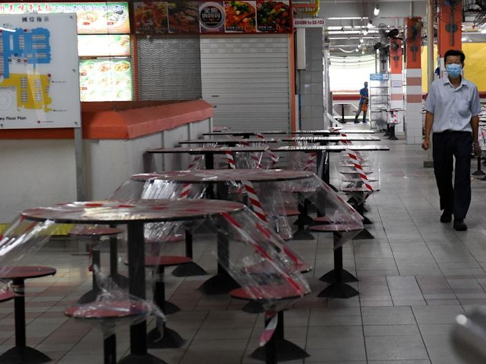 <br>A man walks through a hawker center, where the seats have been cordoned off, in Singapore's Chinatown on April 21, 2020.