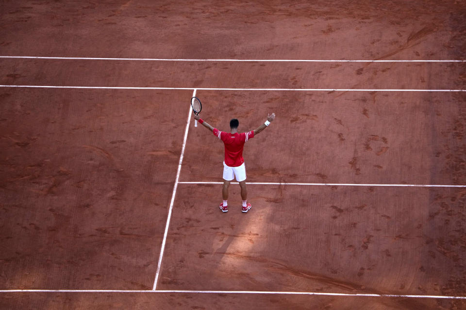 Serbia's Novak Djokovic raises his arms in victory after defeating Stefanos Tsitsipas of Greece during their final match of the French Open tennis tournament at the Roland Garros stadium Sunday, June 13, 2021 in Paris. Djokovic 6-7, 2-6, 6-3, 6-2, 6-4.(AP Photo/Christophe Ena)