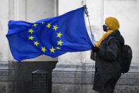 An anti-Brexit demonstrator holds an EU flag in Parliament Square, in London, Wednesday, Dec. 16, 2020. Ursula von der Leyen said Wednesday she saw clear progress in the trade talks with the UK, turning a post-Brexit deal from a fleeting possibility into an ever more realistic possibility. (AP Photo/Alberto Pezzali)