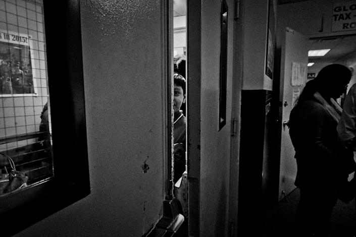 <p>A student peeps through an open door at Kahn's Tutorial's Saturday class in Jackson Heights, Queens, N.Y., in October 2015. Tutorial helps kids get into best NYC high schools — kids of all ethnic backgrounds attend the school. (Photo: Yunghi Kim/Contact Press Images) </p>