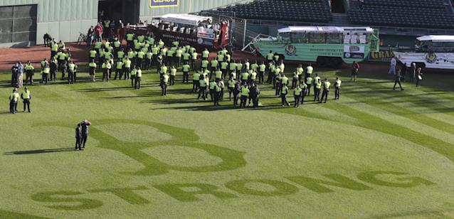 "Boston Police gather near the ""B Strong"" logo, in honor of those affected by the Boston Marathon bombings, at Fenway Park in advance of the Boston Red Sox's championship parade in celebration of the baseball team's World Series win, Saturday, Nov. 2, 2013, in Boston. (AP Photo/Charles Krupa)"