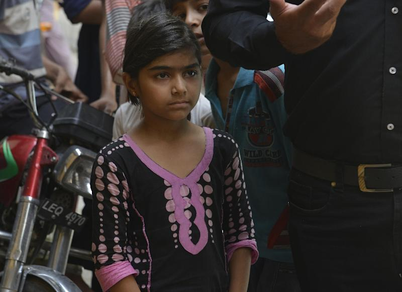 Pakistani schoolgirl Maham, who was taught by Zeenat Bibi, a teenager who was set on fire by her mother, stands outside the house where their teacher lived in Lahore on June 9, 2016 (AFP Photo/Arif Ali)