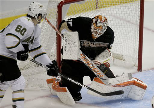 Dallas Stars' Antoine Roussel, left, of France, watches as Anaheim Ducks goalie Viktor Fasth, of Sweden, makes a save during the third period of an NHL hockey game in Anaheim, Calif., Wednesday, April 3, 2013. The Ducks won 5-2. (AP Photo/Jae C. Hong)