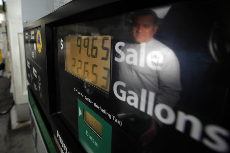Louis Alonzo is reflected on a pump as he fills up a tank at a gas station in La Habra, Calif., Friday, March 16, 2012. Gasoline prices rose again Friday and are now averaging more than $4 in six states plus Washington, D.C. Retail gasoline prices were up a penny on Friday to a national average of $3.831 per gallon, according to AAA, Wright Express and Oil Price Information Service. (AP Photo/Jae C. Hong)