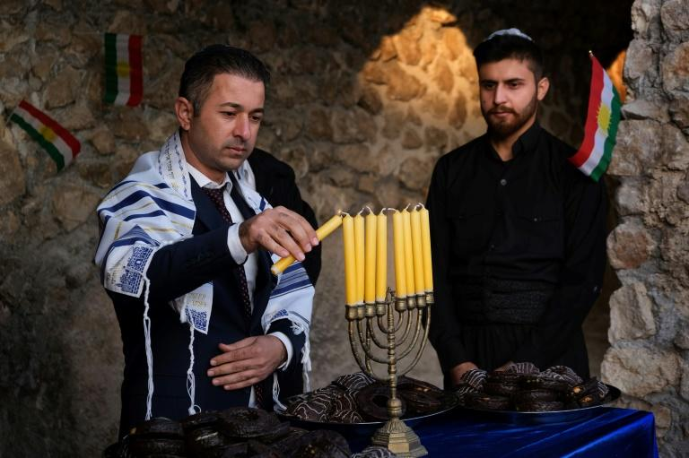 Members of the Jewish community in Iraqi Kurdistan light a menorah for Hanukkah in the town of Al-Qosh