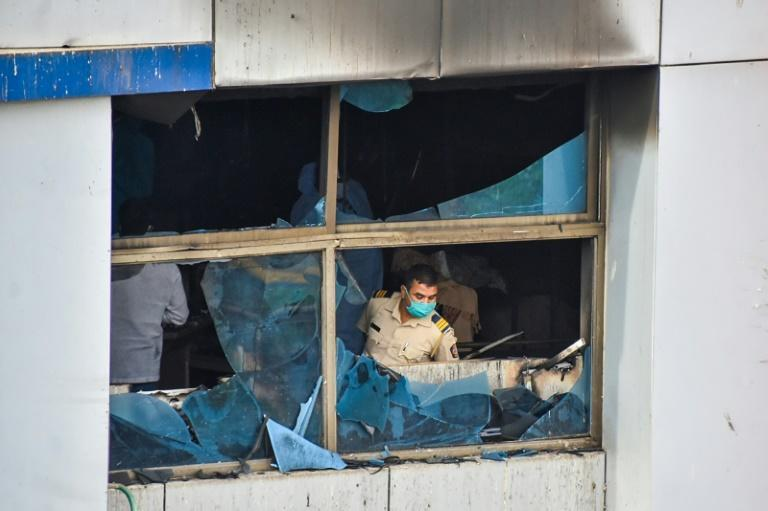 A policeman inspects a burnt out room at Vijay Vallabh Hospital on the outskirts of Mumbai that killed 13 patients