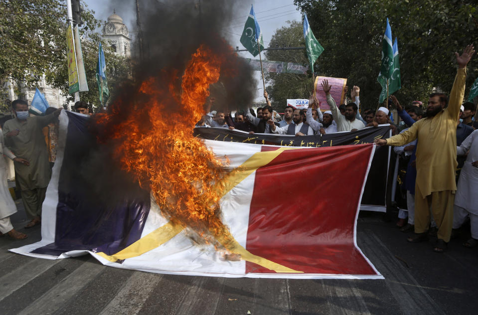 "FILE - In this Oct.30, 2020 file photo, supporters of religious group burn a representation of a French flag during a rally against French President Emmanuel Macron and republishing of caricatures of the Prophet Muhammad they deem blasphemous, in Lahore, Pakistan. A spotlight of suspicion encircled Muslims again even before the latest acts of extremist violence, including two beheadings. French President Emmanuel Macron has forged ahead with a plan to rid Islam in France of extremists, part a project he labels ""separatism,"" a term that makes some Muslims wince. (AP Photo/K.M. Chaudary, File)"