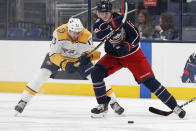 Nashville Predators' Yakov Trenin, left, and Columbus Blue Jackets' Patrik Laine chase the puck during the second period of an NHL hockey game Monday, May 3, 2021, in Columbus, Ohio. (AP Photo/Jay LaPrete)
