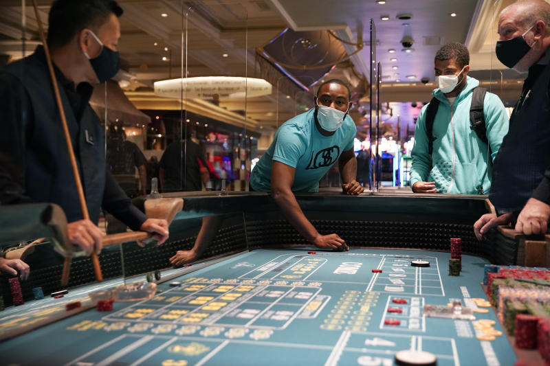 People play craps after the reopening of the Bellagio hotel and casino Thursday, June 4, 2020, in Las Vegas. Casinos in Nevada were allowed to reopen on Thursday for the first time after temporary closures as a precaution against the coronavirus. (AP Photo/John Locher)